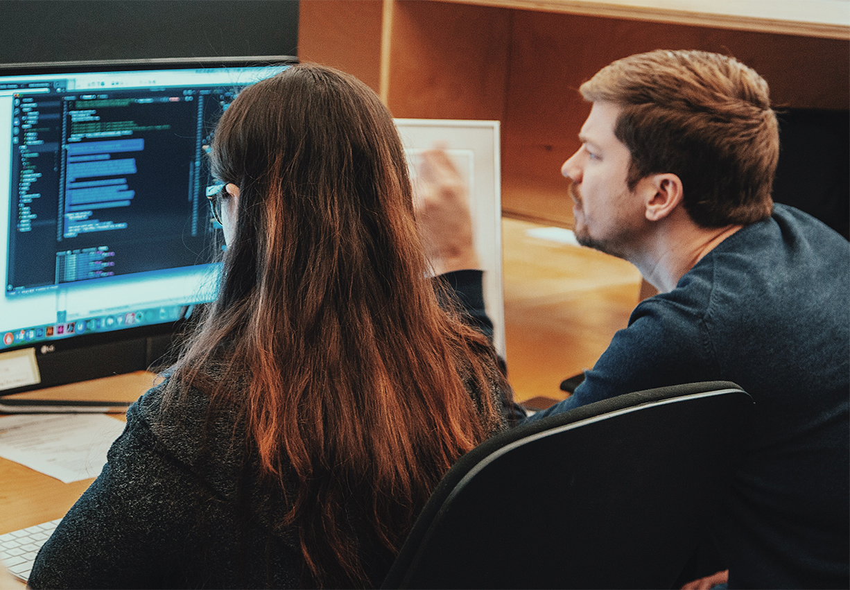 Man and woman looking at code on a computer